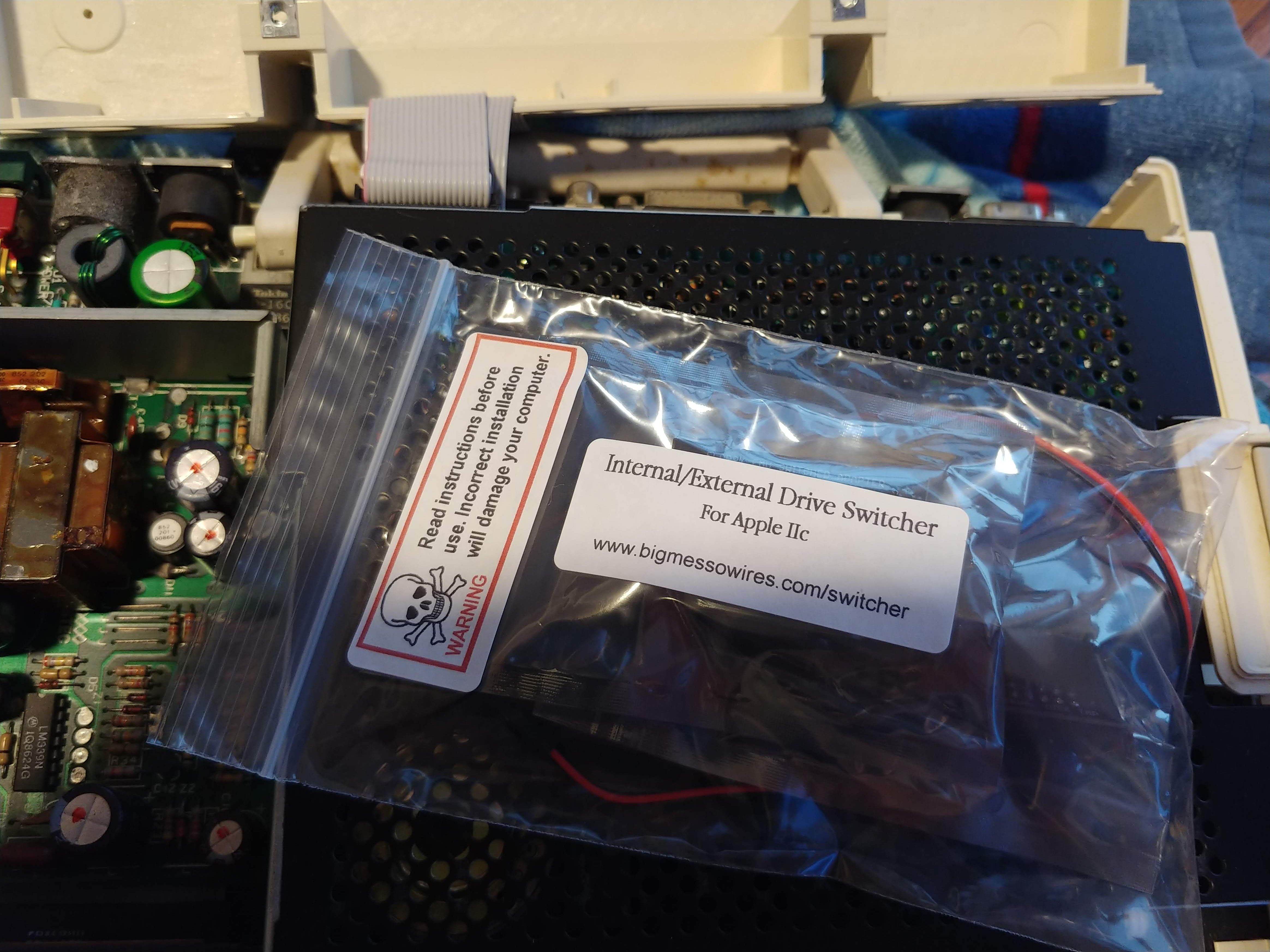 Internal/External Drive Switcher for Apple IIc package (a plastic baggie) on top of the IIc's internal floppy drive.